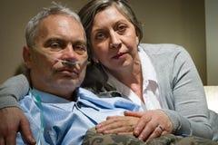 Moglie senior ansiosa che tiene il suo marito malato immagini stock libere da diritti
