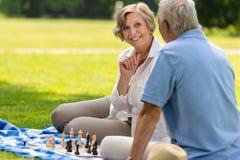 Moglie senior e marito che giocano scacchi all'aperto Immagini Stock Libere da Diritti
