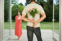 Moglie sorprendente dell'uomo con i fiori fotografia stock libera da diritti