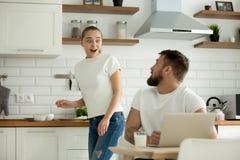 Moglie sorpresa eccitata per sentire le notizie dal marito in cucina immagini stock libere da diritti