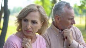 Moglie turbata e marito che si siedono a parte nel parco, equivoco di problema di relazioni fotografia stock