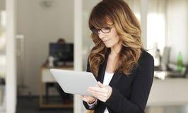 Mogna affärskvinnan med den Digital tableten Arkivbild