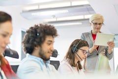 Mogna affärskvinnan som använder den digitala minnestavlan medan operatörer som i regeringsställning arbetar fotografering för bildbyråer