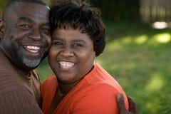 Mogna afrikansk amerikanpar som skrattar och kramar Arkivfoto
