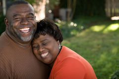 Mogna afrikansk amerikanpar som skrattar och kramar Fotografering för Bildbyråer