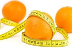Mogna apelsiner och måttband Arkivfoto