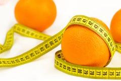 Mogna apelsiner och måttband Arkivfoton