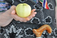 Mogna Apple i handen av en äldre kvinna i en stucken väst för en gå 90 år band för näring för bananhälsomått Närbild arkivfoton