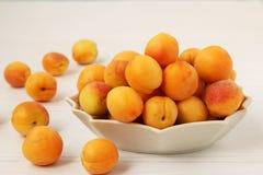 Mogna aprikors lokaliseras på en platta på en vit bakgrund Fotografering för Bildbyråer