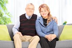 Mogna att krama för par som hemma placeras på soffan Royaltyfri Fotografi