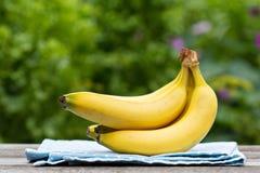 Mogna bananer på trätabellen Royaltyfria Bilder