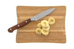 Mogna bananskivor på en skärbräda med kniven Fotografering för Bildbyråer