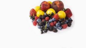 Mogna blåbär, hallon, svarta vinbär, björnbär, jordgubbar, gula plommoner och persikor på vit bakgrund Arkivbilder