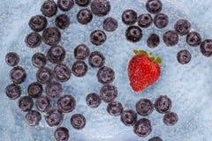Mogna blueberes och jordgubbe i blått vatten med luftbubblor royaltyfri foto
