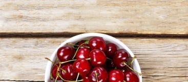 Mogna Cherry In en vit bunke på en träbakgrund, lantlig stil ovanför sikt Royaltyfria Bilder