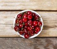 Mogna Cherry In en vit bunke på en träbakgrund, lantlig stil ovanför sikt Royaltyfri Foto