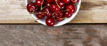 Mogna Cherry In en vit bunke på en träbakgrund, lantlig stil ovanför sikt Arkivfoto