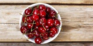 Mogna Cherry In en vit bunke på en träbakgrund, lantlig stil ovanför sikt Arkivbild