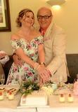 Mogna den bitande bröllopstårtan för par royaltyfria bilder