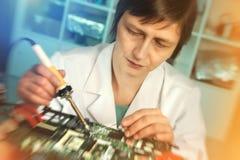 Mogna den caucasian kvinnliga teknikern eller den elektroniska devien för techreparationer arkivbilder