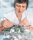 Mogna den caucasian kvinnliga teknikern eller den elektroniska devien för techreparationer arkivbild