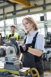 Mogna den kvinnliga arbetaren som arbetar på maskineri med kollegan i bakgrund på fabriken royaltyfri foto