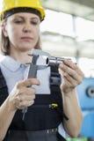 Mogna den kvinnliga arbetaren som mäter metall med klämman i fabrik arkivfoton