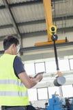 Mogna den manuella arbetaren med den digitala minnestavlafungeringskranen för att lyfta stål i bransch Royaltyfri Fotografi