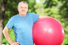 Mogna den sportiga mannen som rymmer en konditionboll parkerar in Fotografering för Bildbyråer