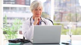 Mogna doktorn som använder en bärbar dator stock video