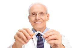 Mogna doktorn som bryter en cigarett i halva arkivbild