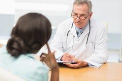 Mogna doktorn som lyssnar till hans patient och tar anmärkningar Fotografering för Bildbyråer