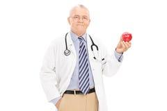 Mogna doktorn som rymmer ett moget äpple Royaltyfri Bild
