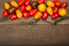 Mogna färgrika körsbärsröda tomater textur och timjan på trätabellen Royaltyfri Fotografi