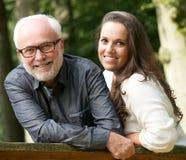 Mogna fadern och barndottern som utomhus ler arkivfoto