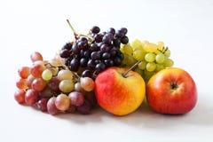 Mogna frukter Äpplen och druvor på en vit bakgrund Royaltyfri Bild