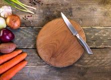 Mogna grönsaker med kniven på trätabellen Organisk mat från f Arkivbilder