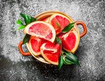 Mogna grapefruktstycken i en bunke arkivfoton