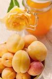 Mogna gula aprikors med aprikosdetoxen dricker med fruktsaft Den gröna bakgrunden Royaltyfri Foto