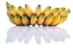 Mogna gula bananer behandla som ett barn på vit isolerad bakgrund med refle Arkivbild