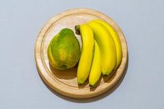 Mogna gula bananer och en pawpaw på uppläggningsfatet arkivbild