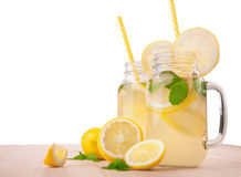 Mogna gula citroner, ny mintkaramell och genomskinliga tillbringare för mineralvatten itu på en ljus trätabell som isoleras på en Royaltyfri Foto