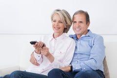 Mogna hållande ögonen på television för par Fotografering för Bildbyråer
