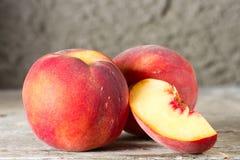 Mogna hela och skivade persikor Arkivfoton