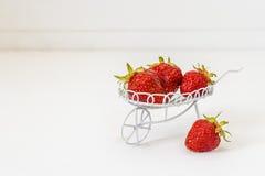 Mogna jordgubbar i en dekorativ trädgårds- spårvagn på en vit tillbaka Royaltyfria Foton
