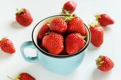 Mogna jordgubbar i en kopp p? en vit bakgrund royaltyfri fotografi