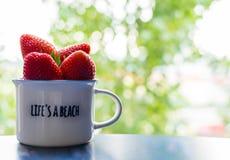Mogna jordgubbar i en vit kopp Royaltyfria Bilder