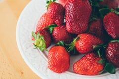 Mogna jordgubbar i en vit platta på en trätabell Royaltyfri Bild
