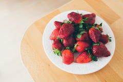 Mogna jordgubbar i en vit platta på en trätabell Arkivfoto
