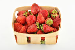 Mogna jordgubbar i träkorgen som isoleras på vit Arkivfoto